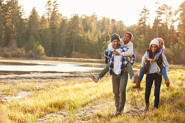 parents giving children piggyback ride on walk by lake - four people stock photos and pictures