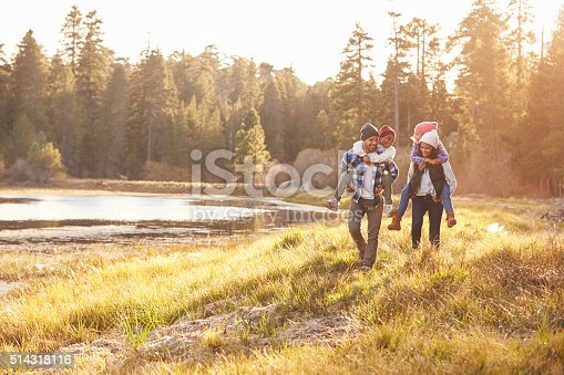 istock Parents Giving Children Piggyback Ride On Walk By Lake 514318116