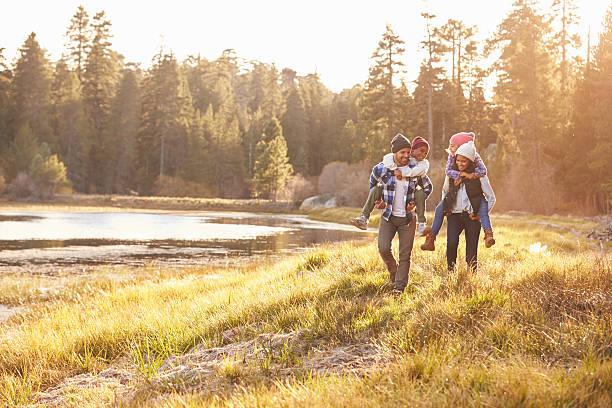 eltern geben kindern huckepack nehmen sie auf spaziergang am see - happy trails stock-fotos und bilder