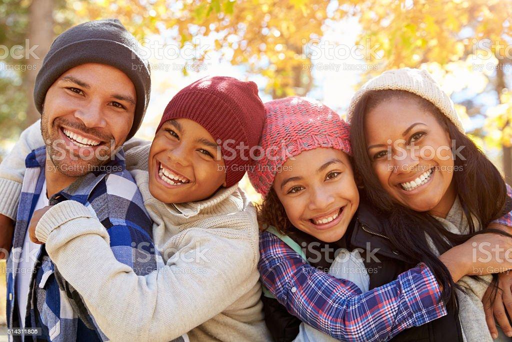 Parents Giving Children Piggyback Ride On Walk In Woods stock photo