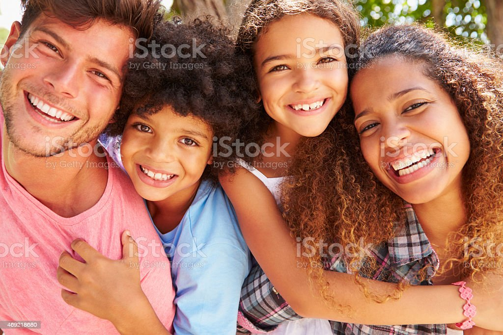 Parents Giving Children Piggyback Ride Outdoors stock photo