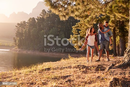 istock Parents Giving Children Piggyback Rides On Walk By Lake 966224144