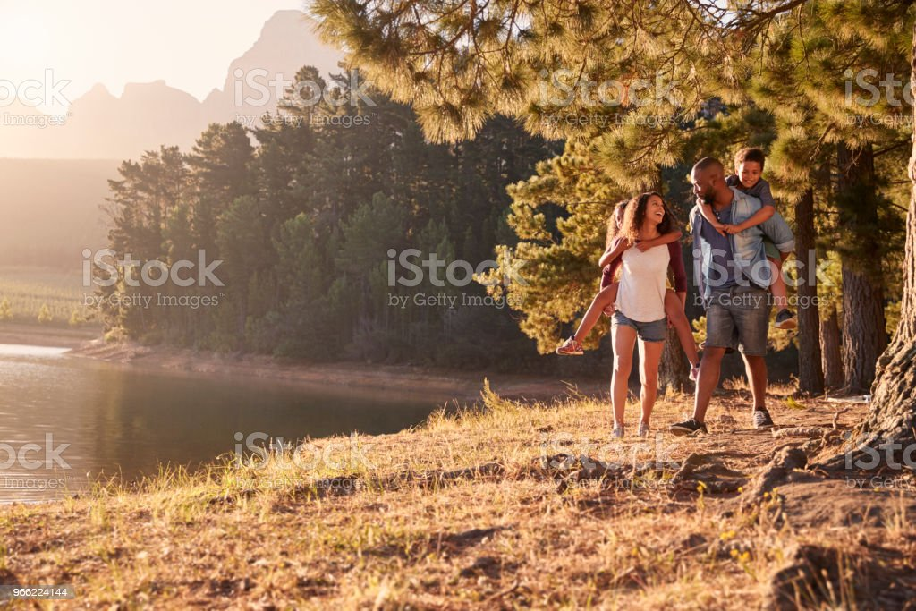 Parents Giving Children Piggyback Rides On Walk By Lake stock photo