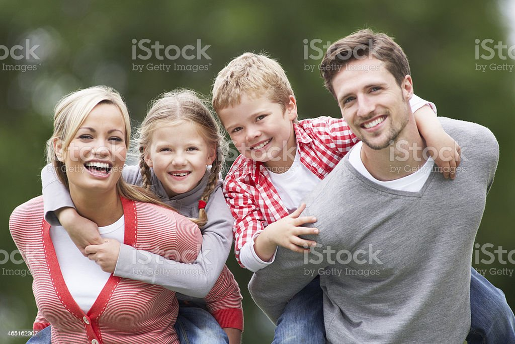 Parents Giving Children Piggybacks In Countryside stock photo