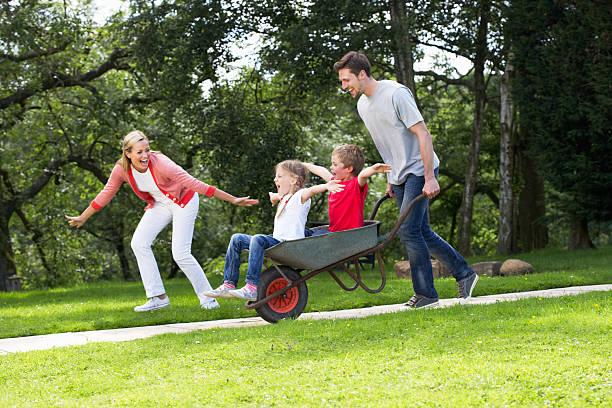 Eltern geben Kindern reiten In Schubkarre – Foto