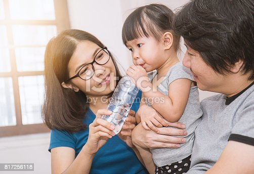 Parents giving little daughter a bottle with drink