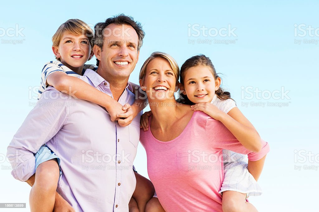 Parents Giving Piggyback Ride To Children Against Clear Blue Sky royalty-free stock photo