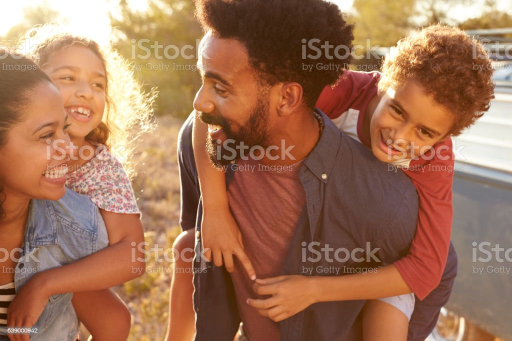 Parents giving their kids piggybacks, waist up, close up stock photo