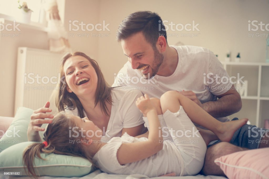 Parents having fun with their little daughter on bed. Family spending time at the morning. stock photo
