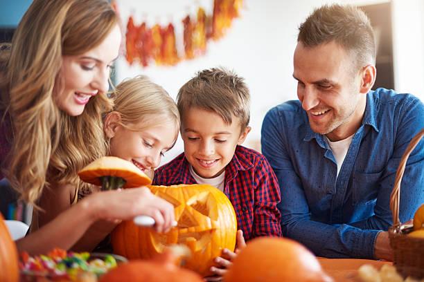 parents helping children in carving pumpkins - schnitzmesser stock-fotos und bilder