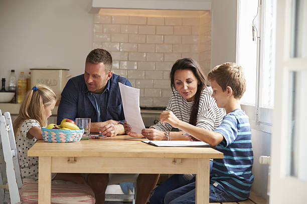 parents helping children with homework at kitchen table - 宿題 ストックフォトと画像