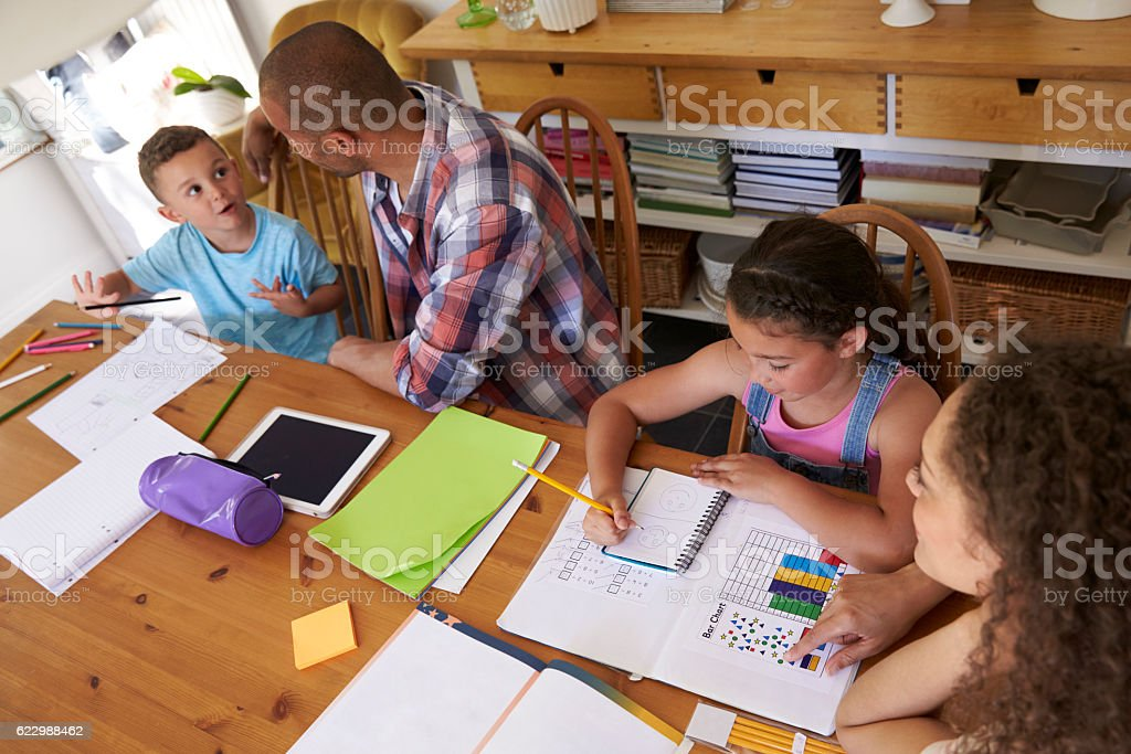 Parents Helping Children With Homework At Table stock photo