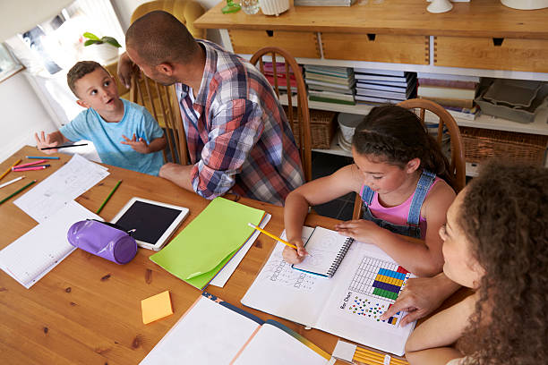 parents helping children with homework at table - homework stock photos and pictures