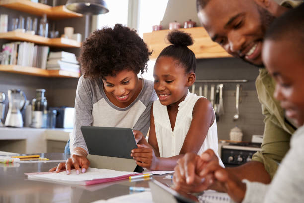 parents helping children with homework in kitchen - homework stock photos and pictures