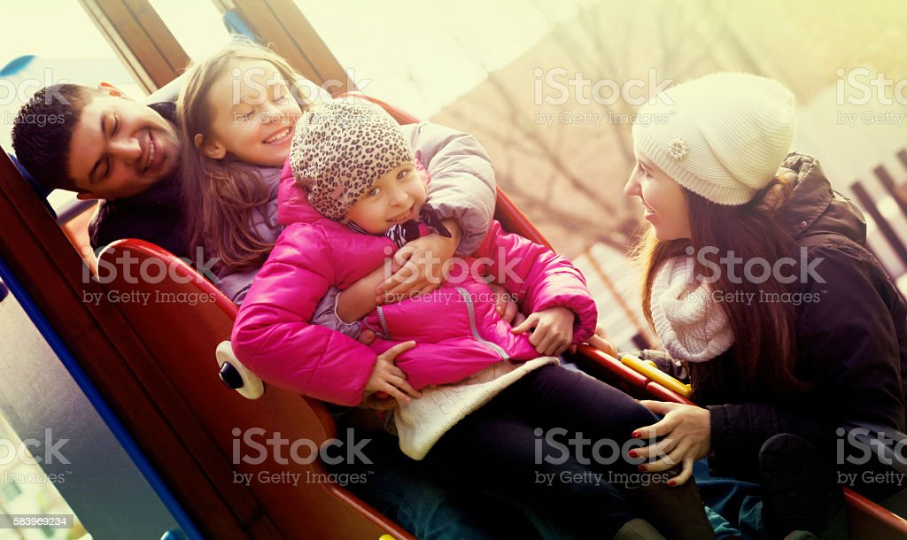 Parents helping kids on slide stock photo