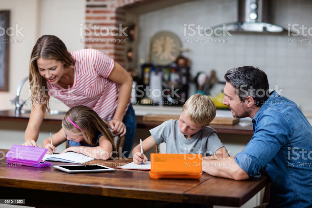Parents helping the kids with their homework stock photo