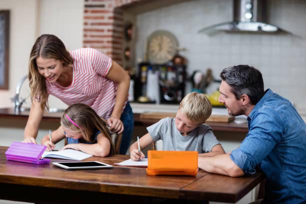 eltern, die kinder bei den hausaufgaben helfen - haushaltsbuch führen stock-fotos und bilder