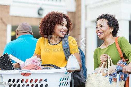 istock Parents helping young African-American woman move 899705158