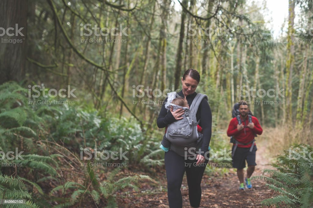 Parents hiking with young children in the forest stock photo