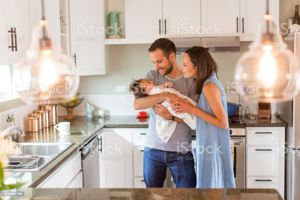 Parents hold baby girl, lovingly in kitchen stock photo