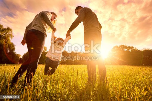 istock Parents hold baby's hands.  Happy family in park evening 588959064