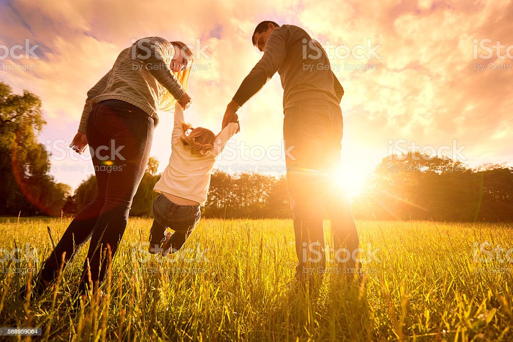 Parents hold baby's hands.  Happy family in park evening - foto de acervo