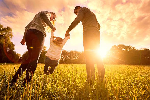 Parents hold baby's hands.  Happy family in park evening ストックフォト