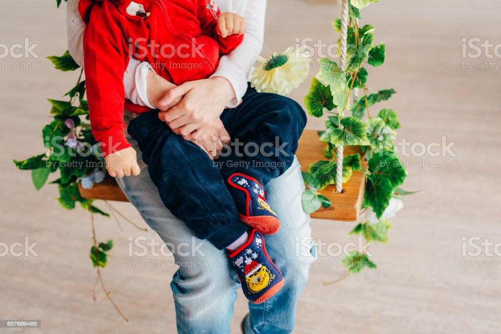 Parents hold the child in their arms. A little child with parent stock photo