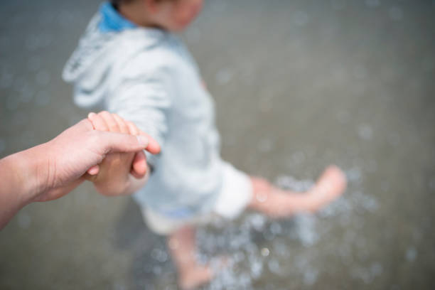Parents holding hands in the sea stock photo