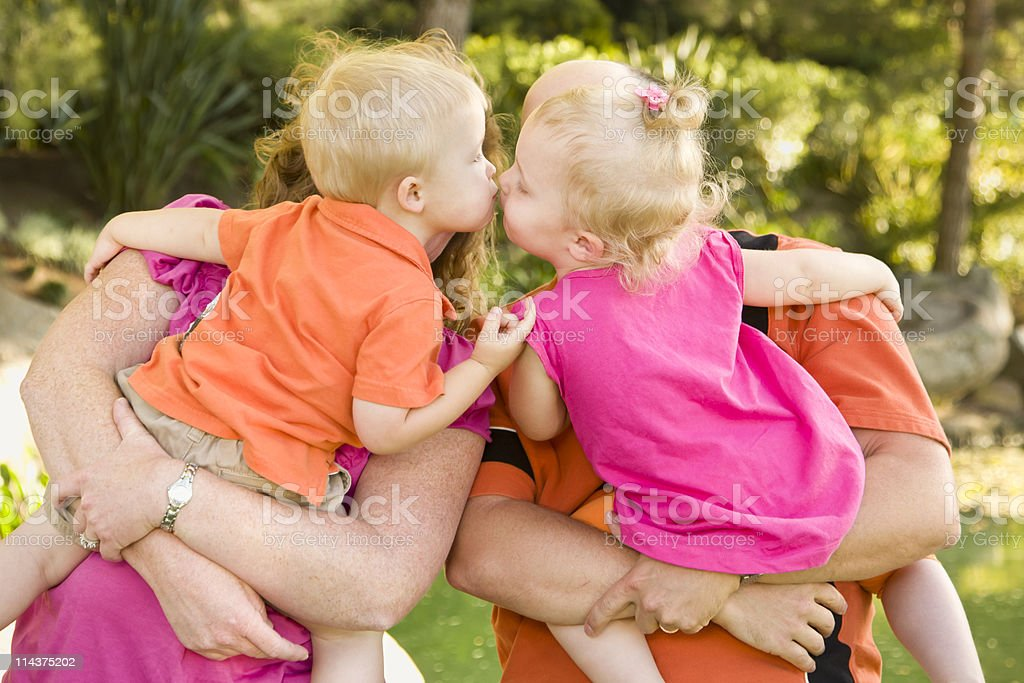 Parents Holding Kissing Brother and Sister Toddlers royalty-free stock photo
