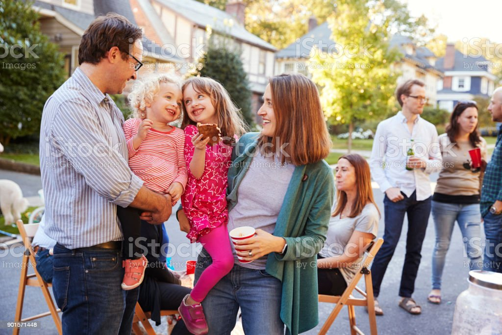 Parents holding their young kids while they eat at a block party stock photo