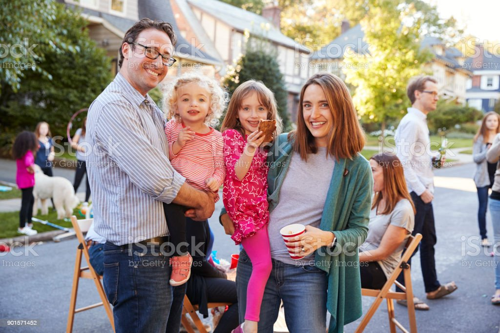 Parents holding young kids smile to camera at a block party stock photo