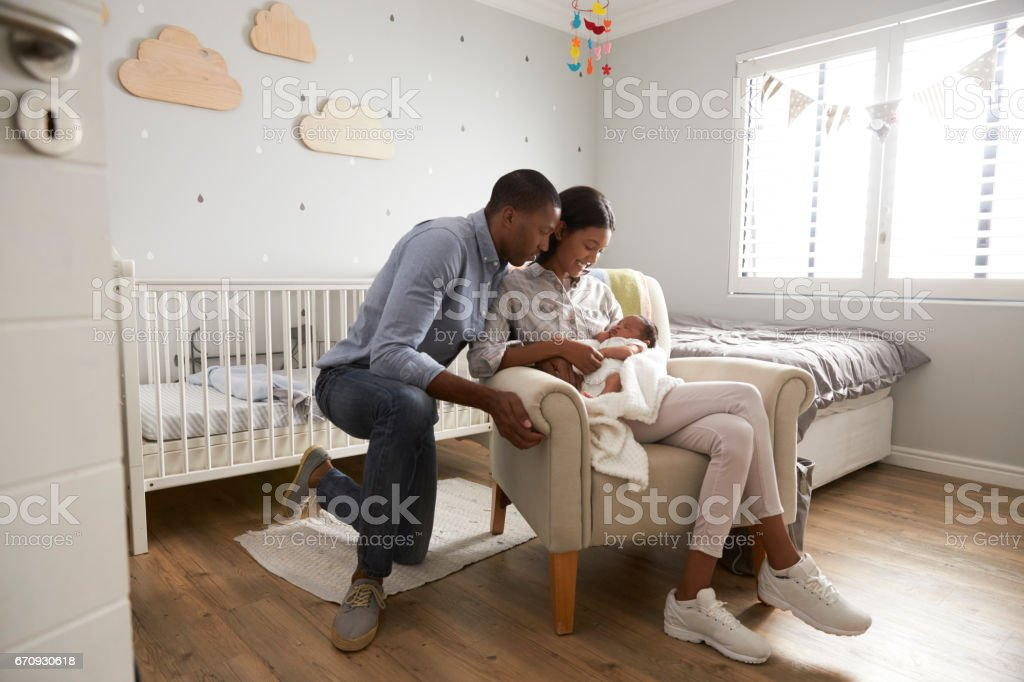 Parents Home from Hospital With Newborn Baby In Nursery stock photo