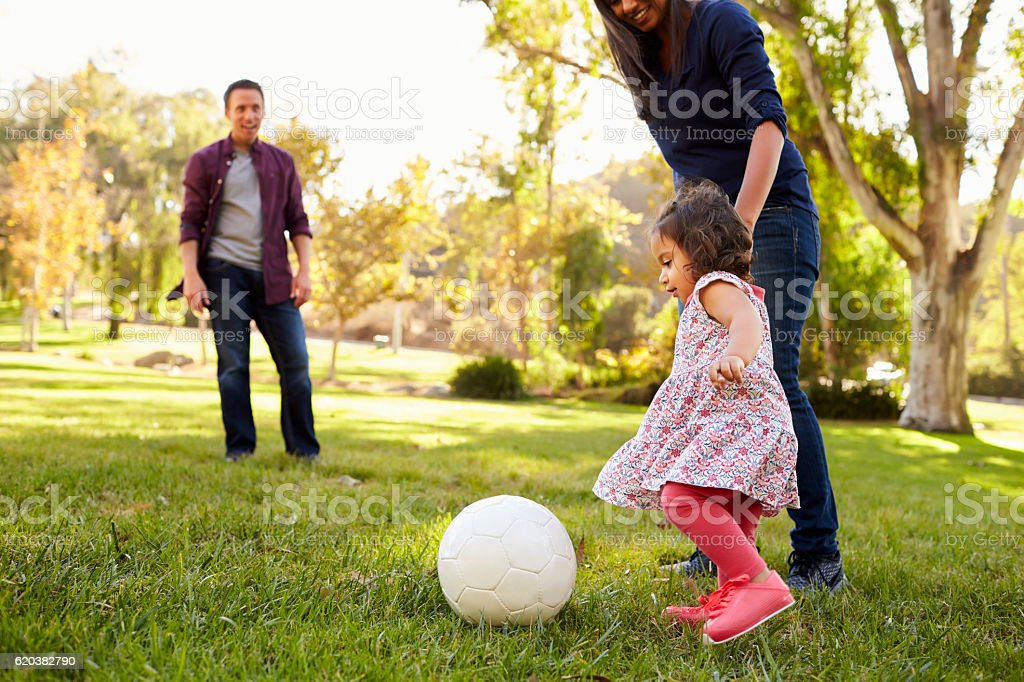 Parents kicking a ball with their young daughter in a park - foto de stock