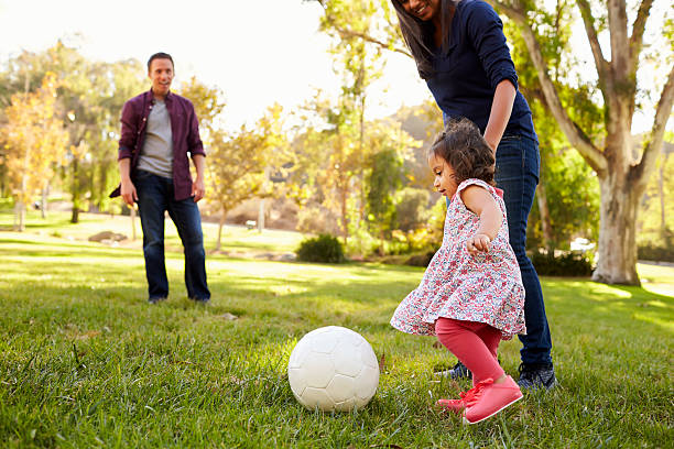 Parents kicking a ball with their young daughter in a park stock photo
