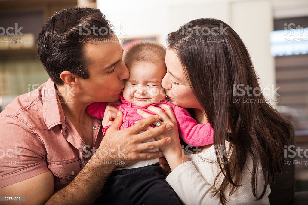Parents kissing baby at the same time stock photo