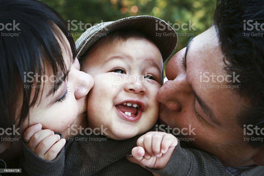 Parents Kissing Child stock photo