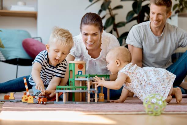 Eltern, die Kinder beim Spielen mit Spielzeug ansehen – Foto