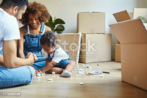 Parents looking at daughter playing with packing peanuts. Happy family of three sitting on hardwood floor in new apartment. They are wearing casuals.