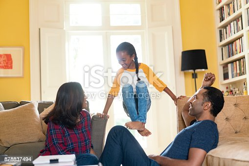 istock Parents looking at girl balancing amidst sofa 878837494