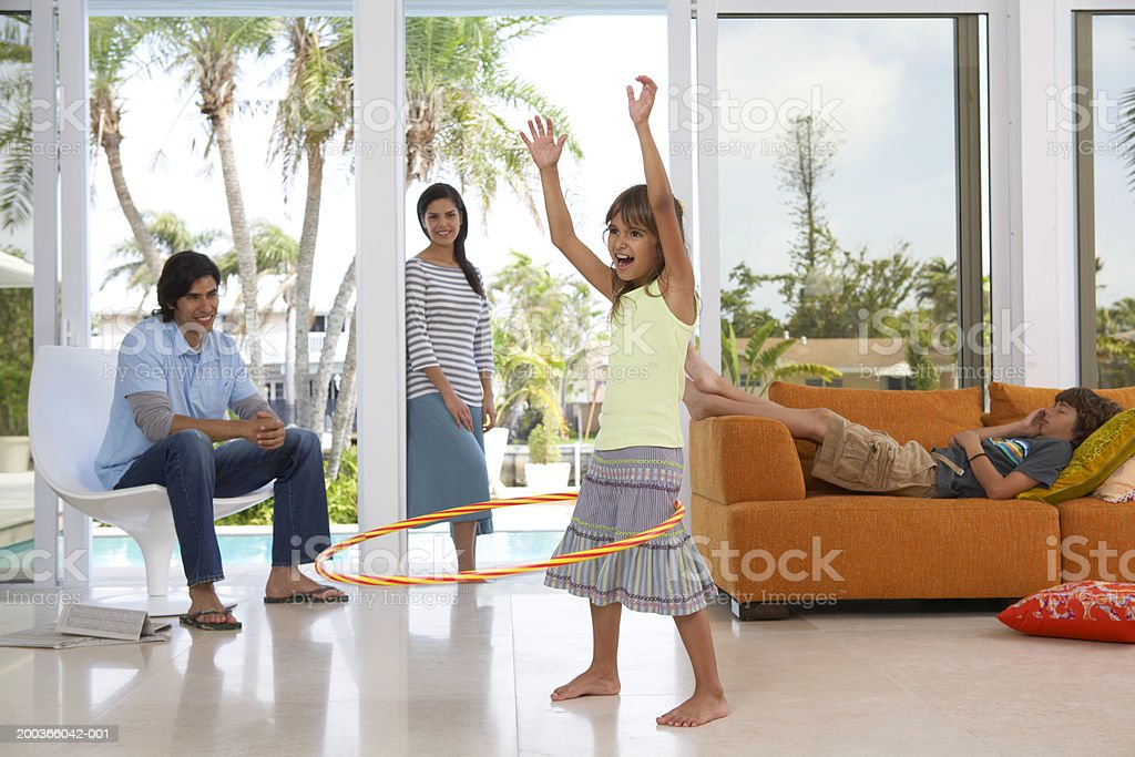 Parents looking at girl (8-10),  with plastic hoop, boy on sofa royalty-free stock photo
