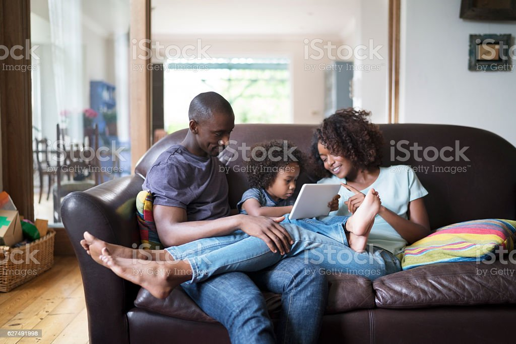Parents looking at son using digital tablet stock photo