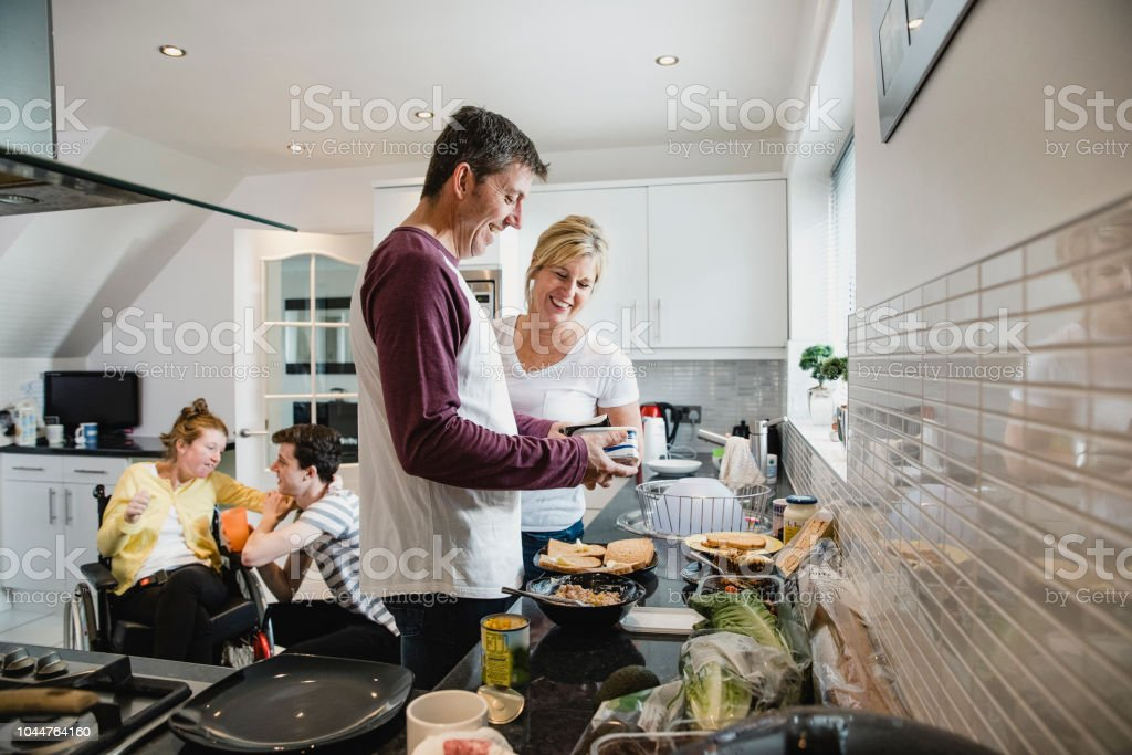 Parents Making Lunch While Son Cares for Disabled Daughter stock photo