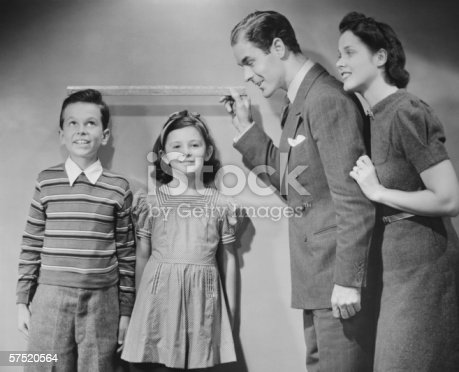 57520540 istock photo Parents measuring children standing against wall, boy (8-9) girl (6-7), (B&W) 57520564
