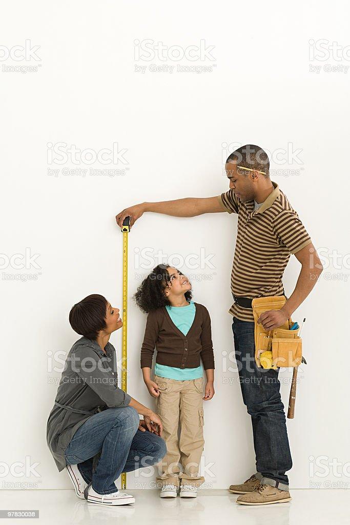 Parents measuring daughter stock photo