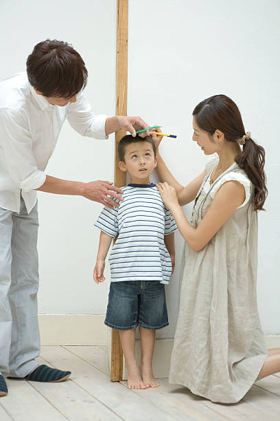 Parents measuring son's height stok fotoğrafı