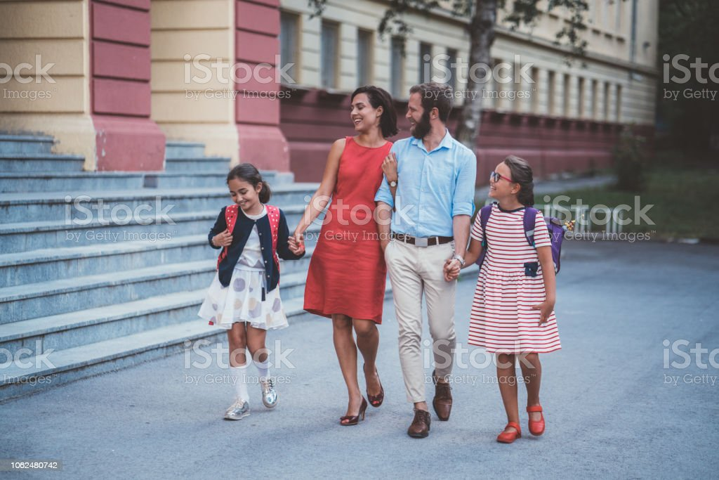 Happy family with two daughters leaving the school building