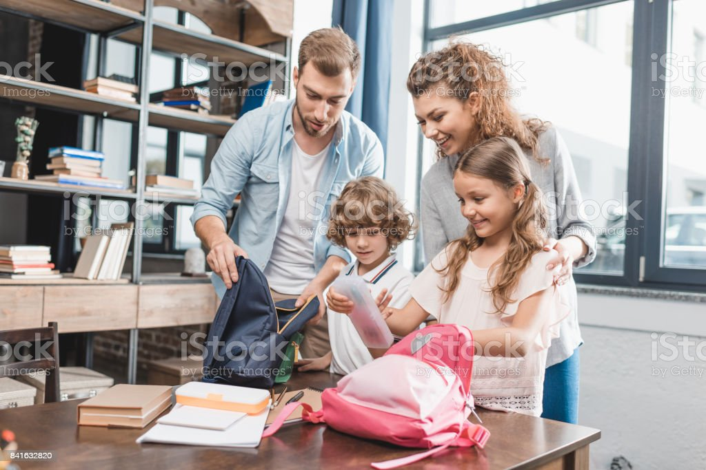 parents packing kids for their first day at school stock photo