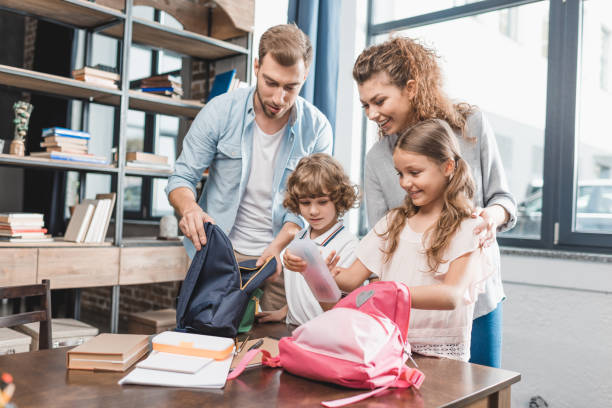parents packing kids for their first day at school - back to school stock pictures, royalty-free photos & images
