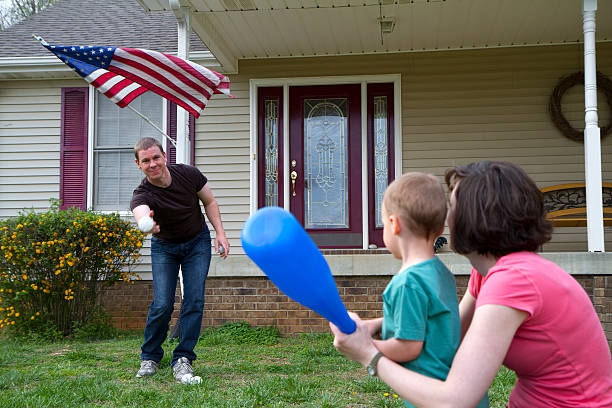 Parents playing baseball with their young son stock photo